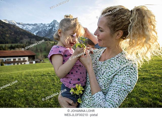 Austria, Tyrol, Walchsee, mother carrying daughter with flowers on an alpine meadow