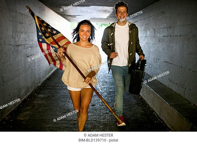 Caucasian couple carrying American flag and boom box in tunnel