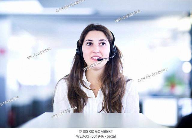 Portrait of young woman with headset in an office