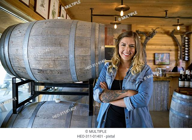 Portrait smiling female vintner with tattoos next to wine barrels in winery tasting room