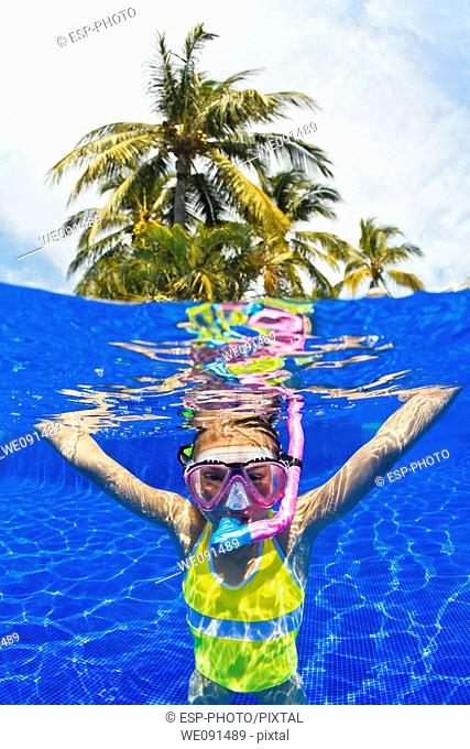 Young girl snorkeling underwater in swimming pool