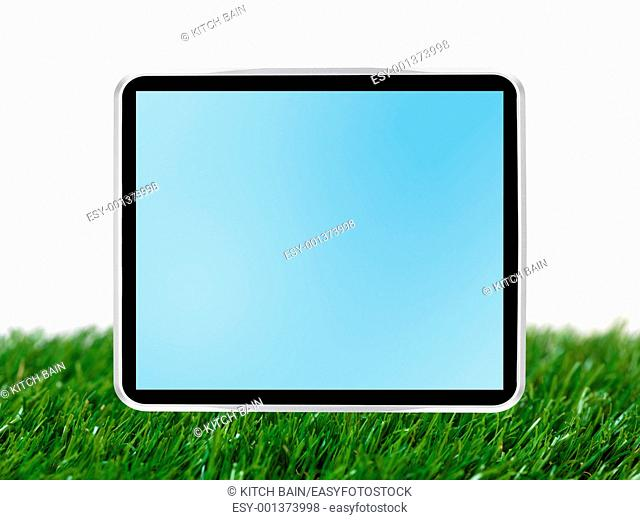 A computer tablet isolated against a grass background