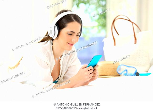 Hotel guest lying on a bed listening to music on summer vacations