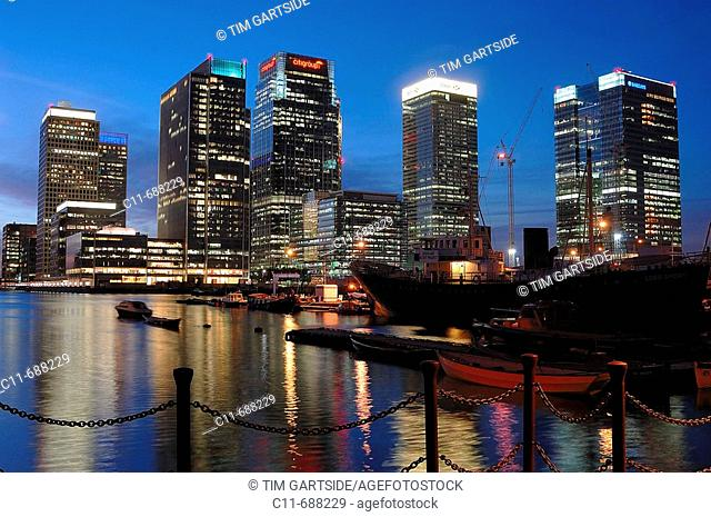 Canary wharf financial district showing skyscraper towers at night dusk evening overlooking water with reflections and ships docked in water isle of dogs