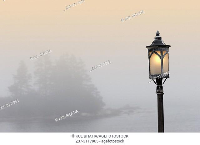 One light stands out like a sentinel as fog gently rolls in across the water in a cove of the Atlantic Ocean, Halifax, Nova Scotia, Canada