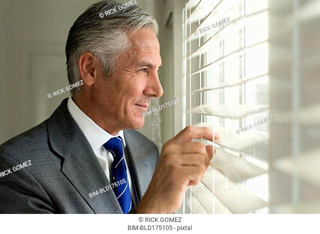 Caucasian businessman looking out window