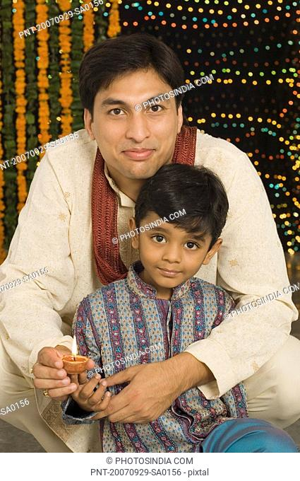 Portrait of a young man and his son holding diwali lamps