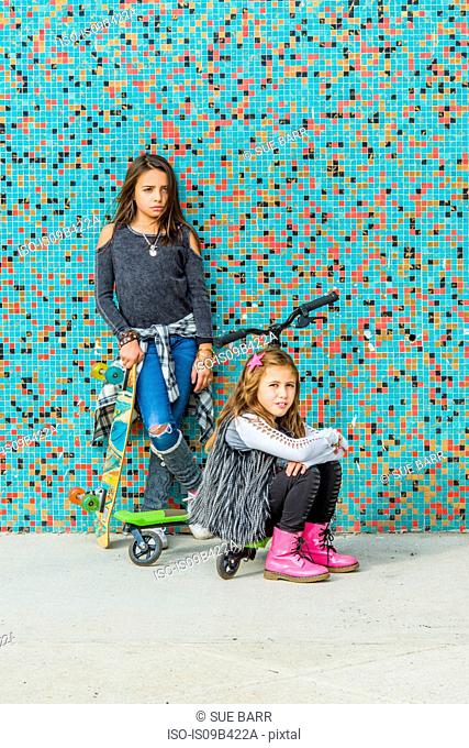 Portrait of two sisters with skateboards and scooter by multi-coloured urban wall