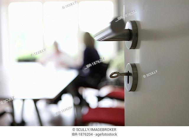 Looking through an open door, conference in an office