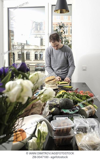Man prepares vegetarian meal in the kitchen