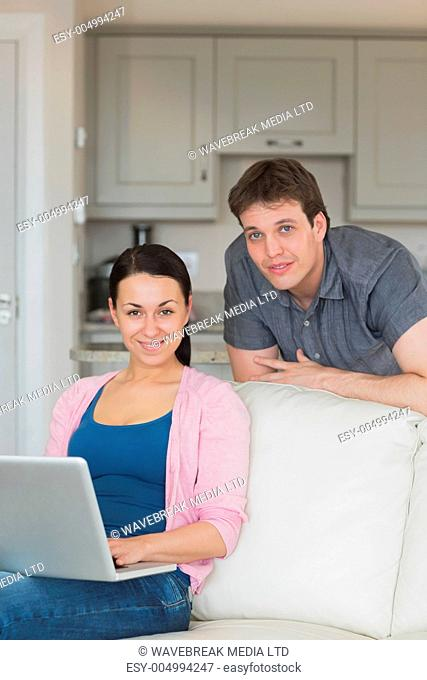 Woman sitting on the couch and uses her laptop while the man stands behind her
