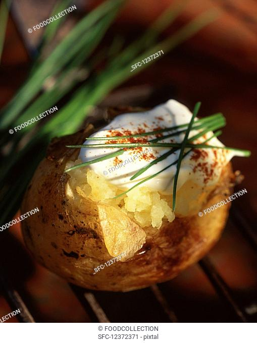 A baked potato with cream fraiche and chives