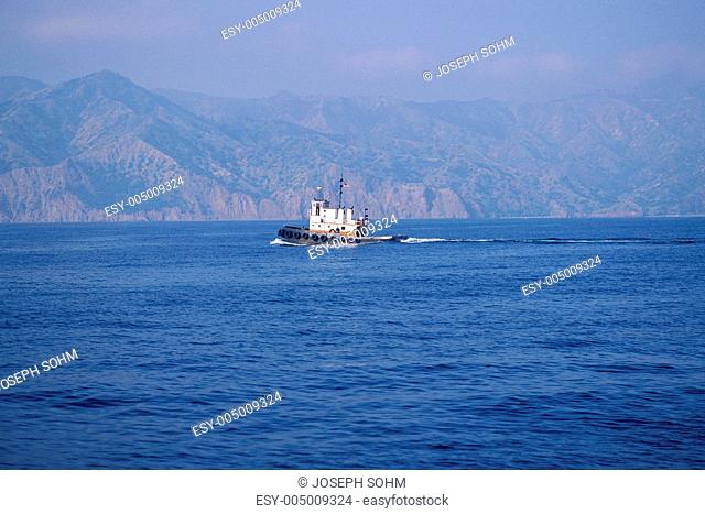Tugboat in water surrounded by hills