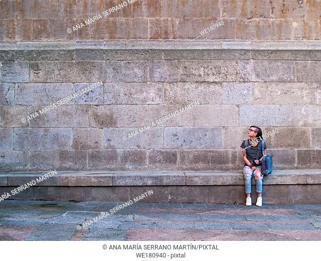 A teenage woman sitting in front of a wall resting