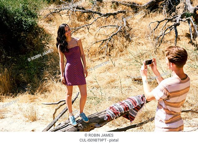 Young man photographing girlfriend in park, Los Angeles, California, USA