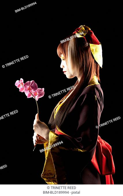 Asian woman in traditional clothing holding flower
