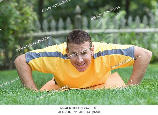 Portrait of a mature man exercising in a garden