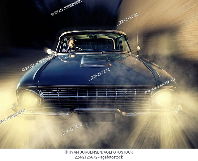 Retro photograph of a detective man driving old blue classic car at fast speed through dark backstreets with headlights beaming. On the trail