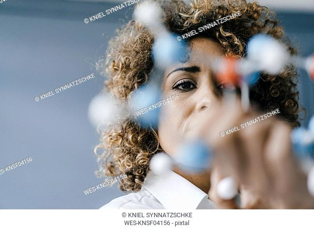 Female scientist looking at molecule model, looking for solutions