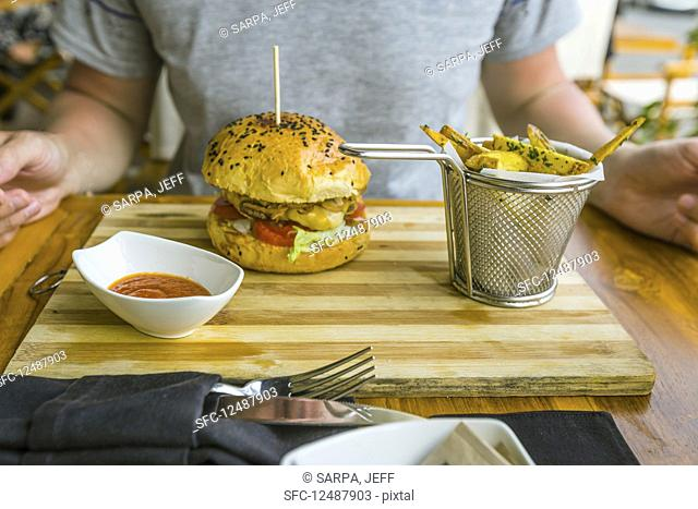 Man is eating burger and french fries in a restaurant