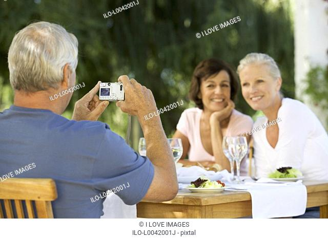 A group of senior couples at a restaurant, man taking picture with digital camera