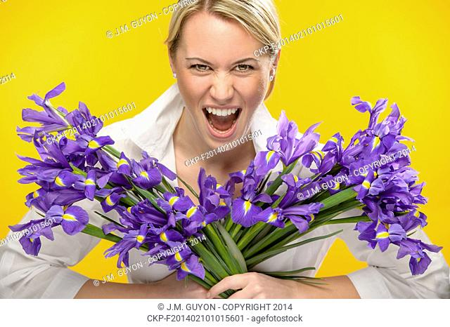Woman with spring iris flower roar on yellow background