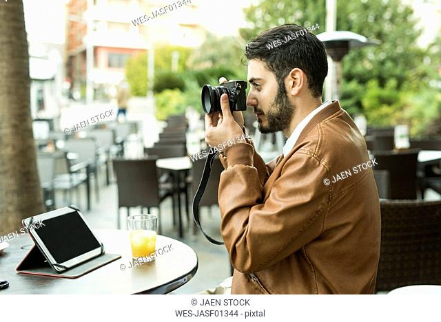 Young man taking pictures at outdoor cafe