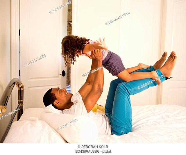 Side view of father lying on bed to lifting up daughter, face to face smiling