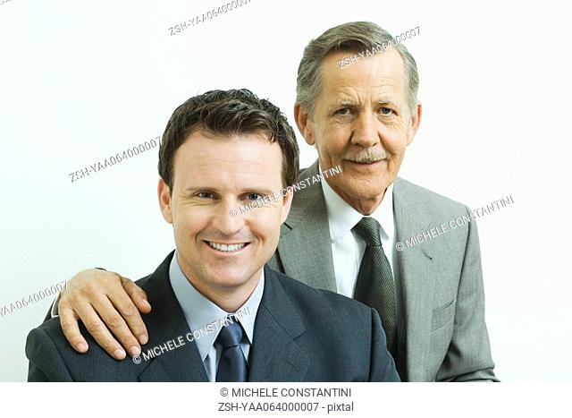 Businessman with hand on associate's shoulder, both smiling at camera, portrait