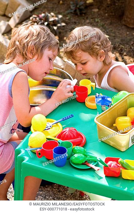 Curious children playing with colorful plastic kitchenware