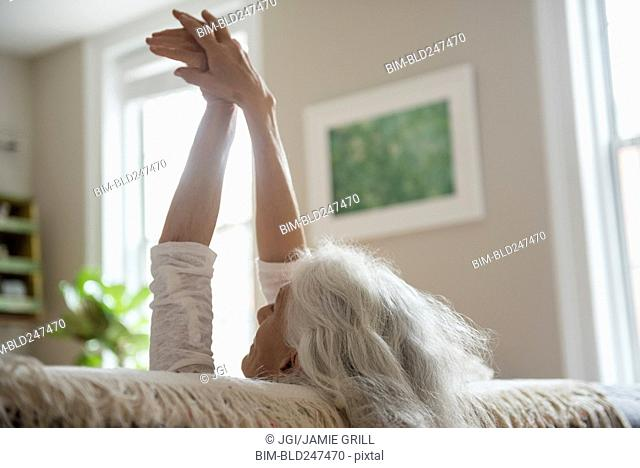 Older woman stretching with arms raised