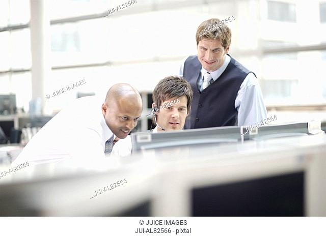 Three businessmen looking at computer monitor