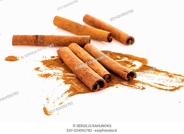 Cinnamon with its dust around it over a white background