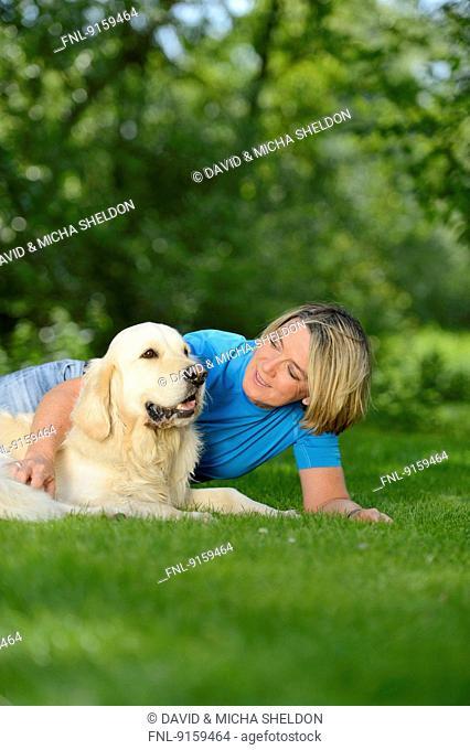 Mature woman with a golden retriever in garden