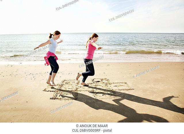 Girls playing hopscotch on beach