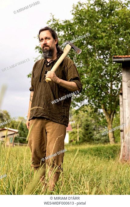 Man with axe standing in the country