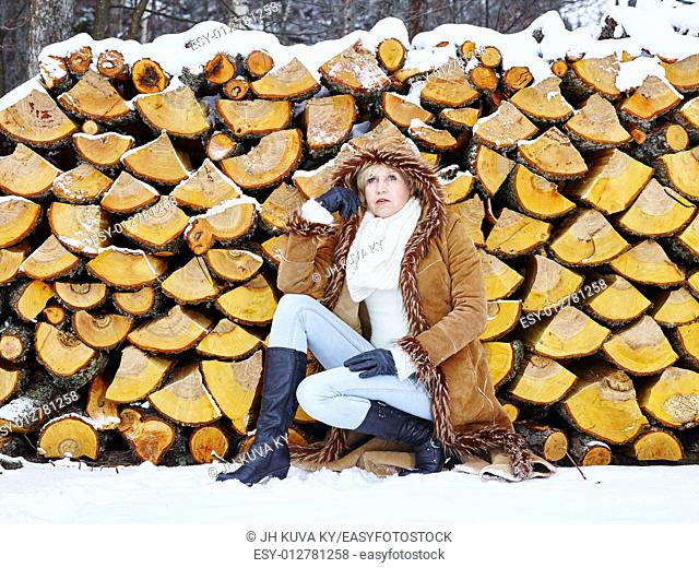 Fashionable mature adult woman wearing winter clothes, rural scene, firewood stack on background. South Finland in January