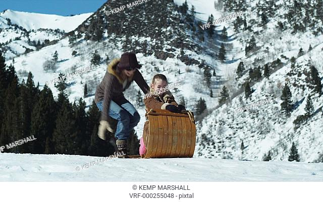 dad pushing his wife and daughter on a toboggan