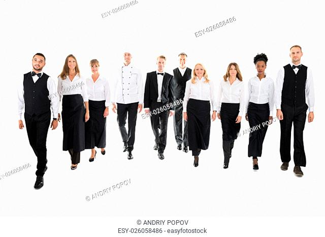Full length portrait of confident restaurant staff walking in row against white background
