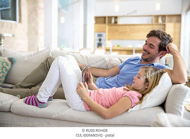 Mature man and daughter reclining on sofa browsing digital tablet