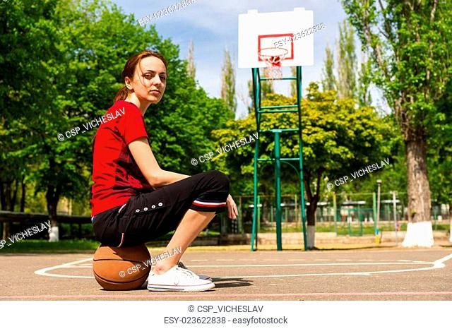 Athletic Woman Sitting on Basketball on Court