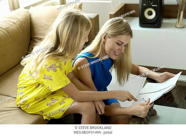 Happy mother and daughter sitting on a couch looking at a notepad together