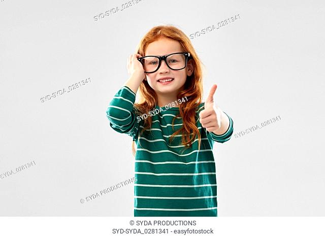 smiling red haired student girl in glasses