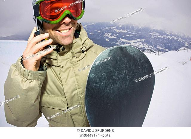 A snowboarder makes a call on his cell phone