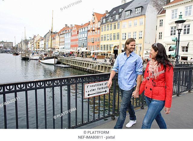 Young couple walking hand in hand on bridge