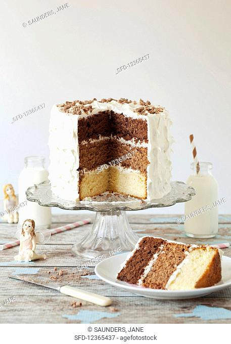 A triple-layered chocolate cake with a slice cut out