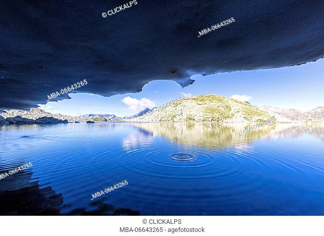 The rocky peaks are reflected in the blue Lago Nero at sunrise Chiavenna Valley Valtellina Lombardy Italy Europe