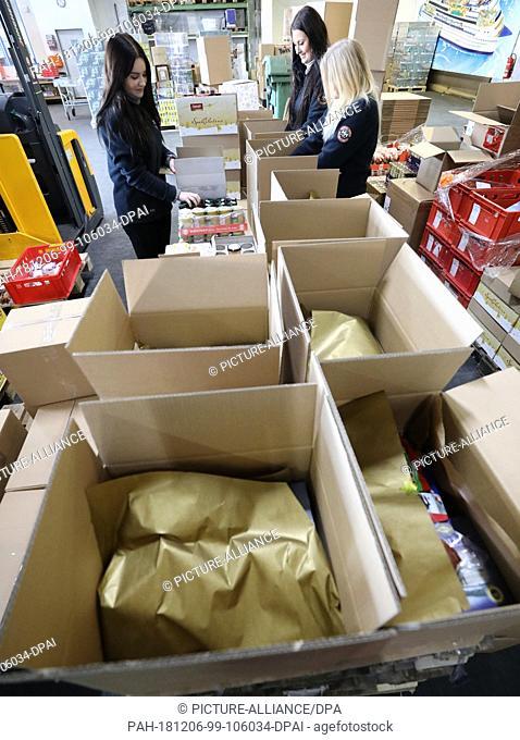 05 December 2018, Mecklenburg-Western Pomerania, Rostock: Amina Marnitz (l-r), Lisa-Sophie Pilgrim and Sophia Driemel are putting together Christmas packages...