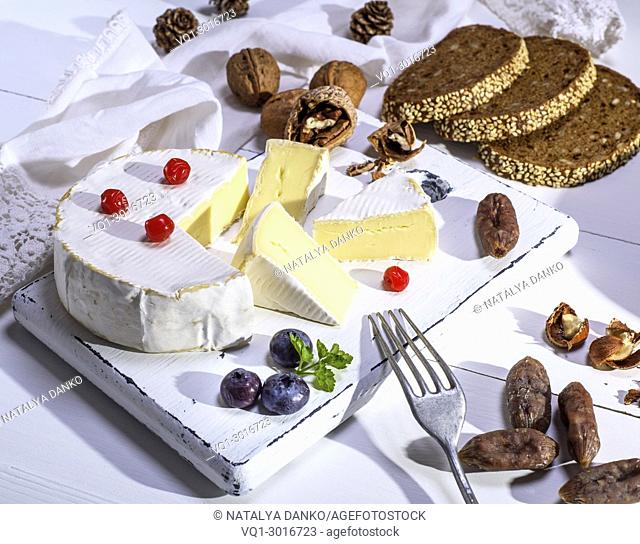 round Camembert cheese, slices of smoked sausage and bread made from rye flour on a white wooden board, white wooden table, top view