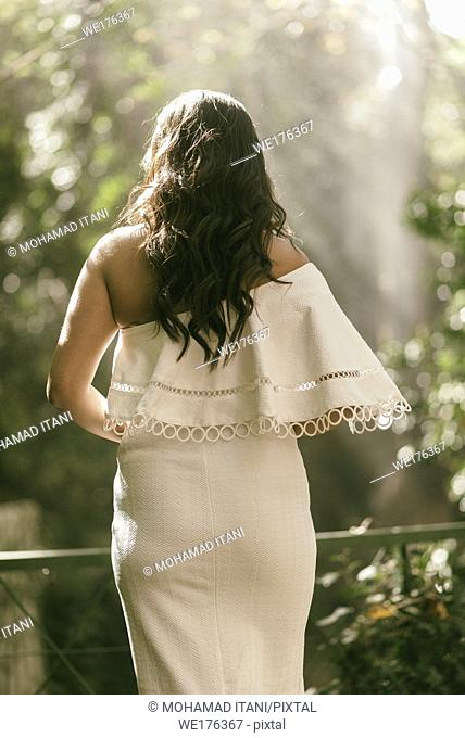 Rear view of a woman in white dress standing outdoors
